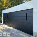 A modern contemporary architectural home with flush-mounted metal paneled garage doors. The double-car and single-car garage doors features horizontal metal panels that camouflage into the surrounding metal clad wall panels around the garage door openings. Both flush mount garage doors are finished in matte black to blend in seamlessly with the architectural paneling of this Beverly Hills home.