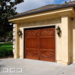 A single-car overhead garage door in a French Provincial style. The wooden garage door boasts an exquisite European style with a faux arch top detail. The top third of the door consists of two hand-forged scrolls that were beautifully inlaid into the wood. The mid third section is composed of vertical tongue and groove planks that simulate French bead board and the bottom third of the garage door is accentuated with diamond trim work that is reminiscent of French architecture. A set of custom levers give the door the total effect of out-swing carriage doors!