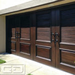 Modern Mediterranean double-car garage door in a dark stained mahogany wood. The top two-thirds is composed of horizontal thick-louver blades while the bottom one-third boasts rectangular raised panels. Both, the upper and lower, sections of the wooden garage door are embellished with a moulding detail. Two sets of iron-forged decorative pulls accentuate the carriage style of the overhead sectional garage door!