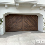Authentic Spanish Colonial double-car garage door in clear vertical grain cedar. The garage door features a Herringbone tongue and groove plank design with perimeter trim work. The corner portion of the trim mimics the home's existing corbel designs. One-third from the bottom is a horizontal trim piece the finishes off the carriage door design of the door. Alone or with decorative iron hardware this door is a fabulous design for a Santa Barbara style home!