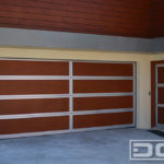 Eight panel double car garage door in Parklex, faux wood panels with a silver steel trim on the perimeter of each panel. A unique modern contemporary garage door for a high end beachfront property.