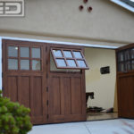 Seen in this image is a double car garage door conversion. The door configuration consists of a four panel bi-folding configuration that parts in the middle with two panels folding out to the right and two panels bi-folding to the left. Each bi-folding panel boasts a functional awning window at the top with a six glass pane configuration, truly divided by mullions. The open window shows a bug screen that will keep bugs out when open but let ventilation into the converted garage. The bottom panel of the system is composed of three vertical recessed panels that give this bi-folding carriage door configuration its Craftsman Architectural Style. To accentuate the beauty of the clear alder wood grain we stained the door in a warm, golden color similar to natural cedar wood.
