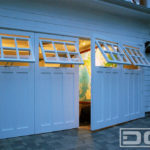Custom architectural out-swing carriage doors in white with functional, awning windows. Handcrafted in composite materials with clear glass windows with six panes divided by true mullions. Two large door panels swing out on this double car garage door opening.