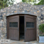 Pictured in this image is a Tuscan style carriage garage door in a two-leaf out-swing format. The carriage doors are slightly arched at the top to match the garage opening. The carriage door panels are divided into three sections with the top quarter consisting of vertical tongue and groove planks in variant widths. Below that section you'll see a quarter of the panel with a large window fitted with antique seedy glass and vertical iron balusters. The bottom half of the door panels is, again, composed of vertical tongue and groove planks in variant widths to match the very top of the panels. The carriage doors are handsomely crafted out of rustic alder wood with an oil rub finish which gives the automatic carriage doors an old world look with the convenience of modern day automation. These doors can be opened at the push of a button!